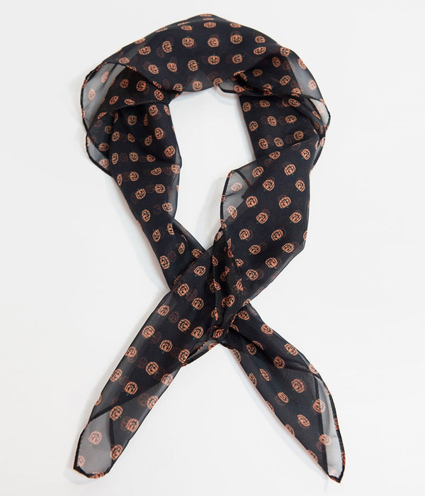 This is a black pinup style chiffon hair scarf that has orange pumpkins on it.