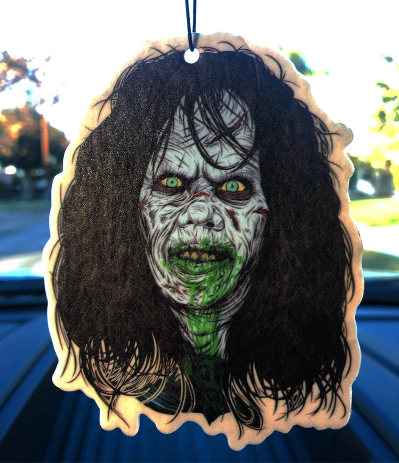 This is a Regan Exorcist air freshener and she has dark hair and green puked vomit on her face.