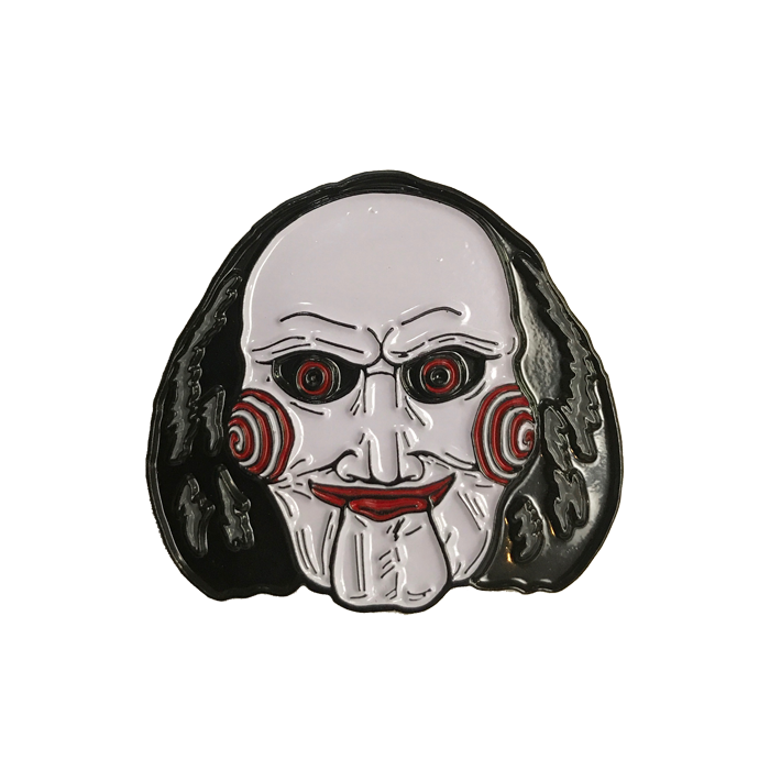 This is a Saw Billy enamel pin from Trick Or Treat and he has a white face, black hair, red lips and eyes and bullseye cheeks.