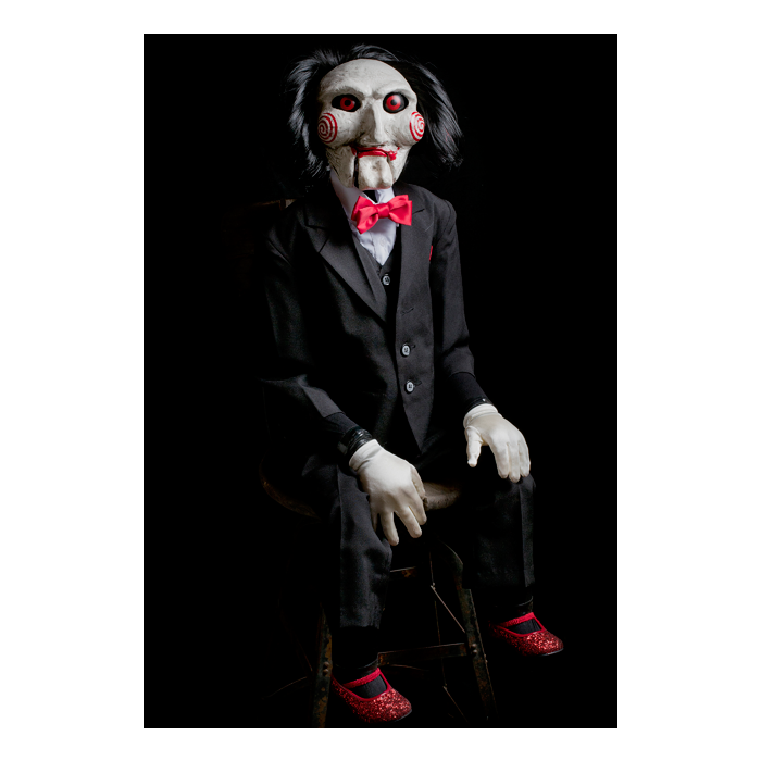 This is a Saw movie Billy puppet prop by Trick Or Treat and he is wearing a black suit, red shoes, with a red bow tie, white gloves and has red eyes, lips, black hair and bullseyes on his cheeks and is sitting in a chair..
