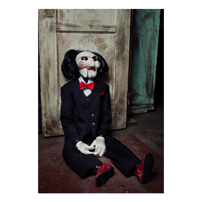 This is a Saw movie Billy puppet prop by Trick Or Treat and he is wearing a black suit, red shoes, with a red bow tie, white gloves and has red eyes, lips, black hair and bullseyes on his cheeks and is sitting on the floor.