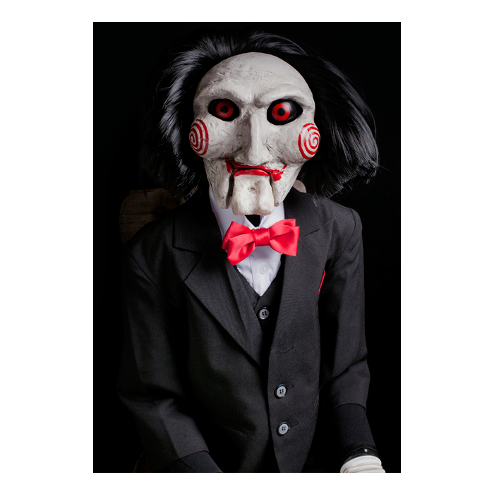 This is a Saw movie Billy puppet prop by Trick Or Treat and he is wearing a black suit with a red bow tie and has red eyes, lips and bullseyes on his cheeks.