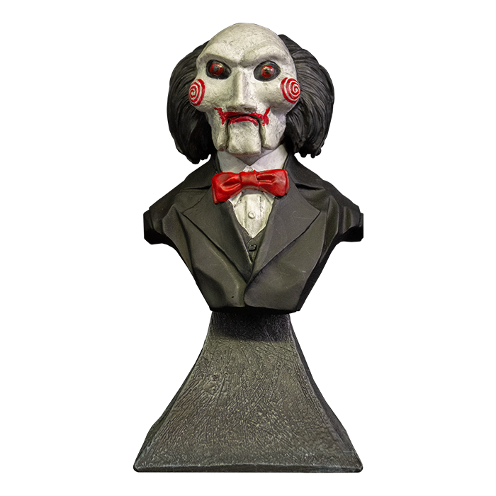 This is a Saw Billy mini bust and he has a white face, red eyes and lips, red cheek bullseyes, red bowtie, black suit and he is on a grey stand.
