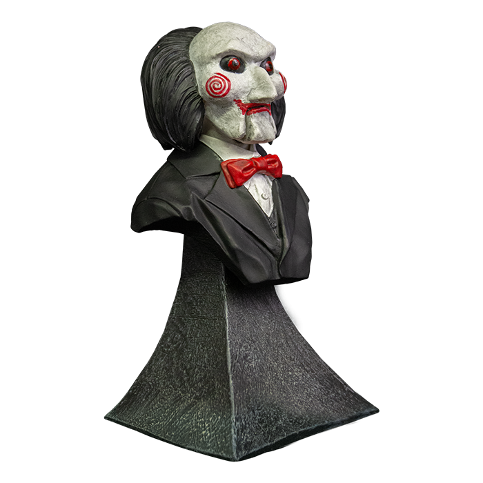 This is a Saw Billy mini bust and he has a white face, red eyes and lips, red cheek bullseyes, red bowtie, black suit , black hair and he is on a grey stand.
