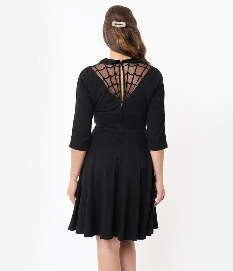 This is a black Unique Vintage flare dress that has a spiderweb neck, Peter Pan collar, 3/4 sleeves and the model is wearing a silver hair clip.