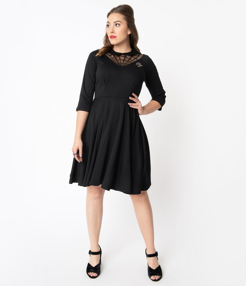 This is a black Unique Vintage flare dress that has a spiderweb neck, Peter Pan collar, 3/4 sleeves and the model is wearing black shoes.