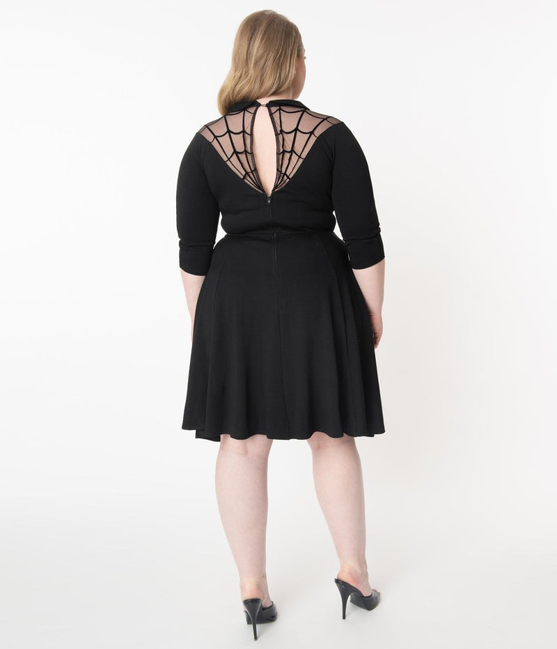 This is a black Unique Vintage flare dress that has a spiderweb neck, Peter Pan collar, 3/4 sleeves and the plus model is wearing black shoes and her hair to the side.