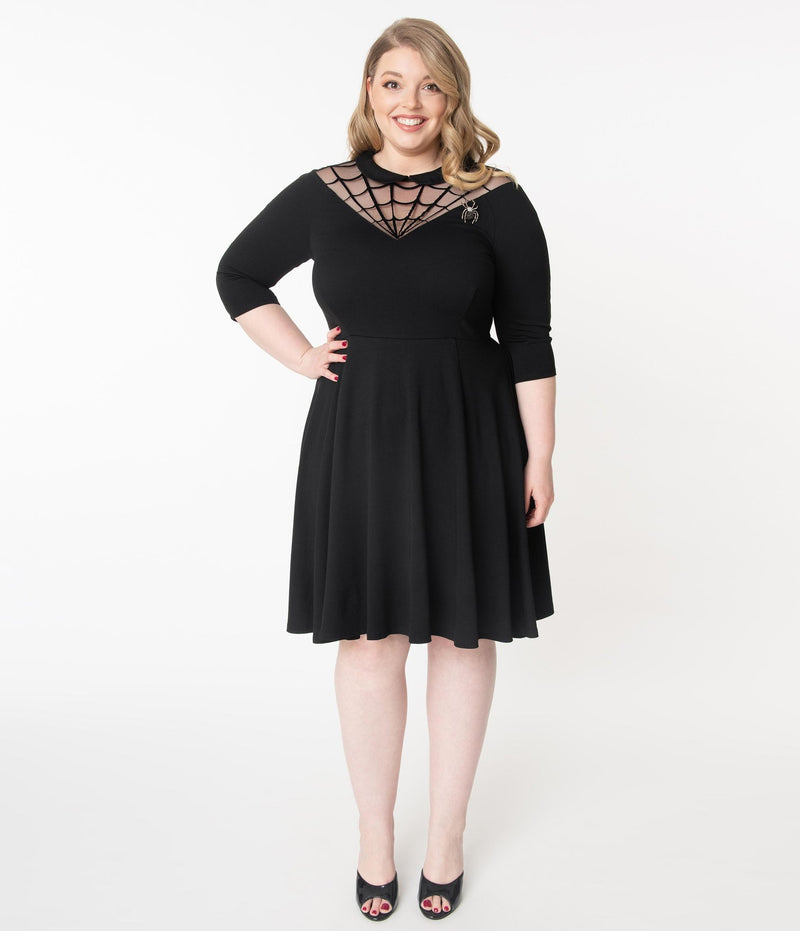 This is a black Unique Vintage flare dress that has a spiderweb neck, Peter Pan collar, 3/4 sleeves and the plus model is wearing black shoes.
