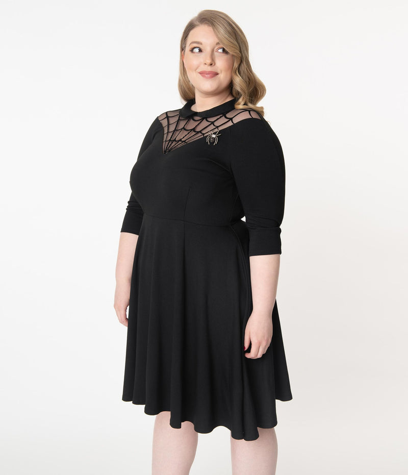 This is a black Unique Vintage flare dress that has a spiderweb neck, Peter Pan collar, 3/4 sleeves and the plus model is smiling and has a spider brooch.