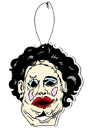 This is a 1974 Texas Chainsaw Massacre Pretty Woman air freshener and it is a tan face with dark hair, blue eye shadow and red lips.