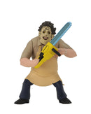 Leatherface action figure is standing in front of a white background, while wearing a yellow apron and holding a yellow chainsaw.