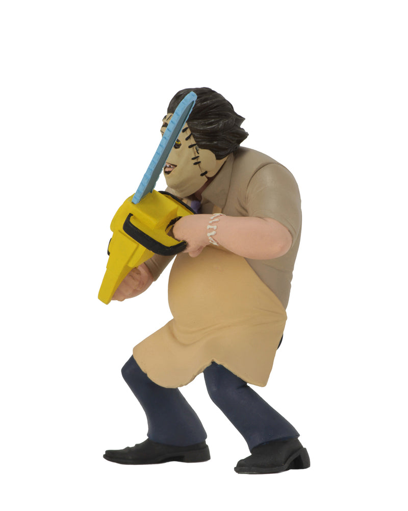 Leatherface Tooney Terror is standing in front of a white background in a 1974 killing mask, while wearing a yellow apron and holding a yellow chainsaw.