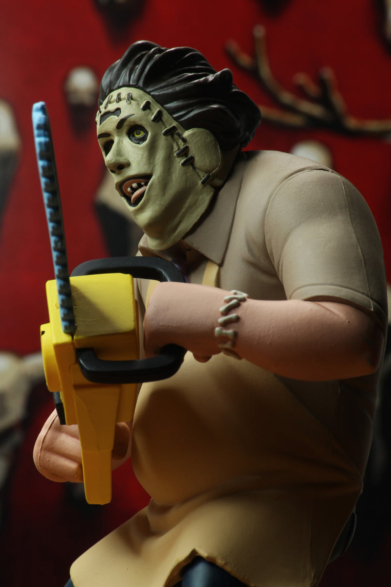 Leatherface is standing in front of a red wall, while wearing a yellow apron and holding a yellow chainsaw.