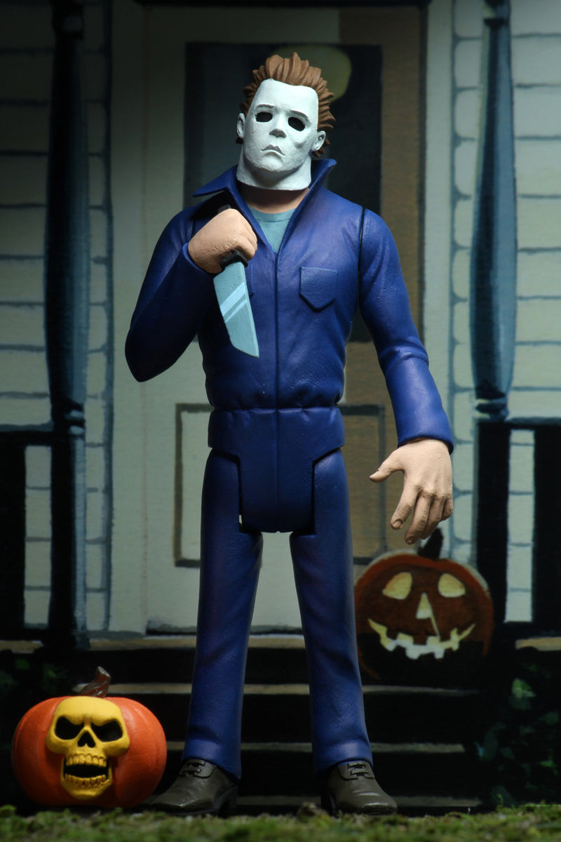 Michael Myers is standing in blue coveralls on a front porch of a house in Haddonfield, holding a knife, with a pumpkin at his feet.