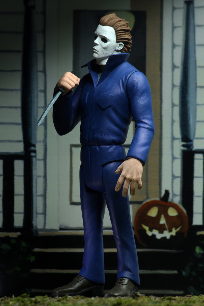 Michael Myers action figure is standing in blue coveralls on a front porch of a house in Haddonfield, holding a knife, with a pumpkin at his feet.