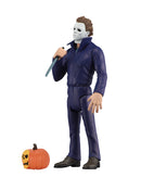 Michael Myers NECA action figure is standing in blue coveralls with a white background, holding a knife, with a pumpkin at his feet.