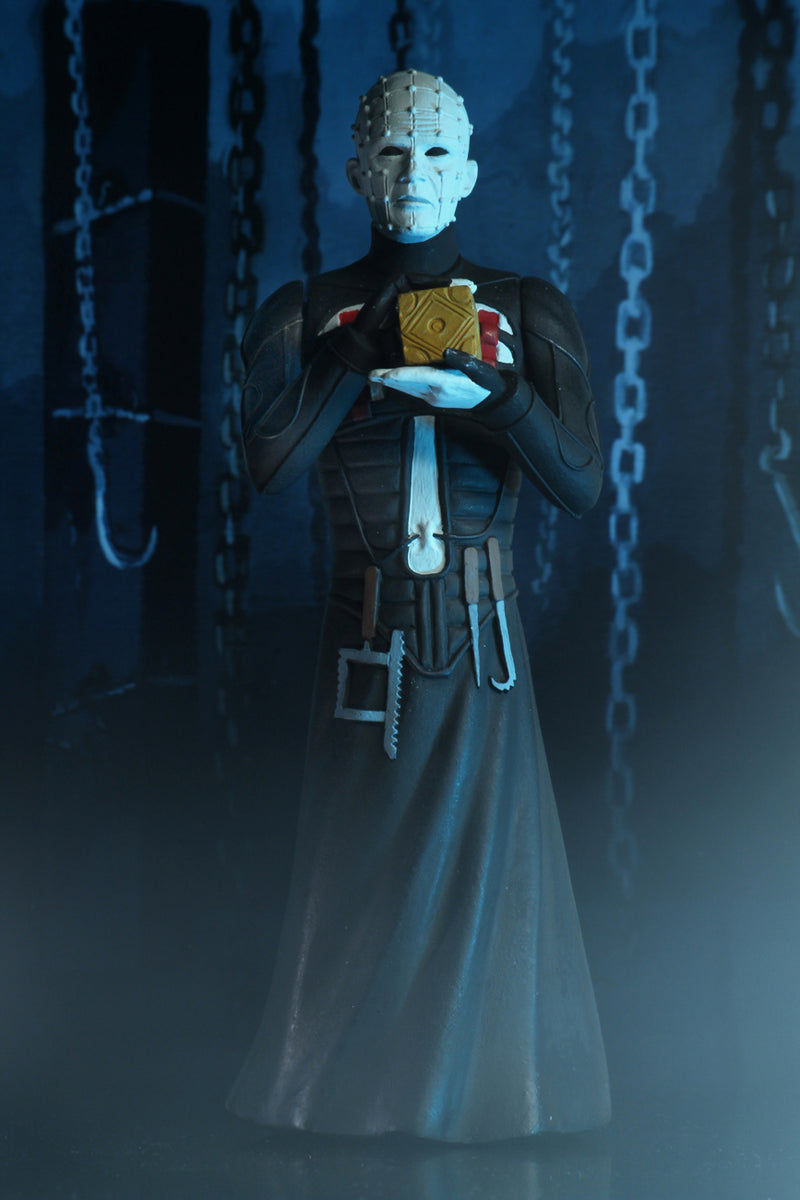 Pinhead is standing in a black dress outfit with tools hanging from it, holding a brown box, with blue lighting.