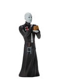 Pinhead NECA Tooney Terror action figure is standing in a black dress outfit with tools hanging from it, holding a brown box, with white lighting.