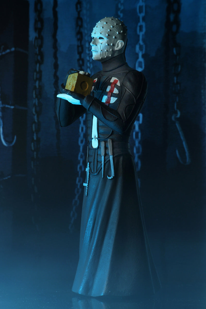 Pinhead action figure is standing in a black dress outfit with tools hanging from it, holding a brown box, with blue lighting.