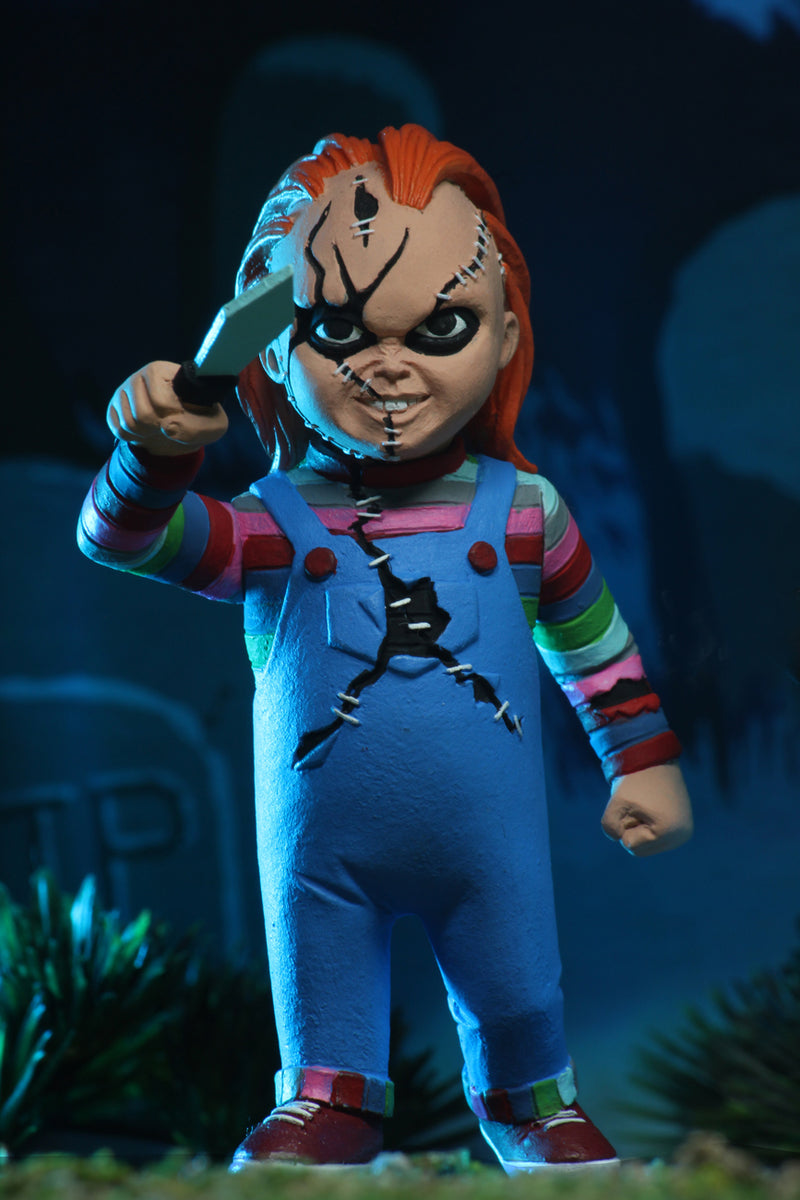 Chucky NECA action figure is wearing a striped shirt with coveralls, holding a knife and has scars on his face.