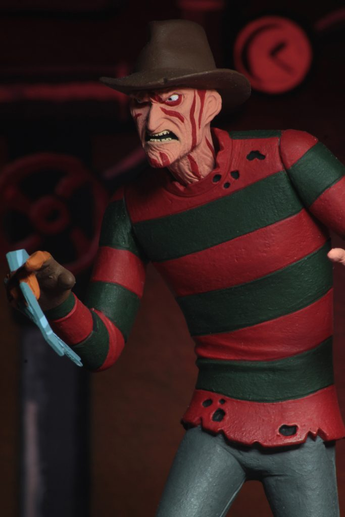 This is a NECA Toony Terror action figure of Nightmare On Elm Street Freddy Krueger, who is wearing a brown hat, red and green sweater with holes and grey pants.