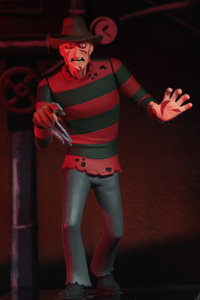 This is a NECA Toony Terror action figure of Nightmare On Elm Street Freddy Krueger, who is wearing a brown hat, red and green sweater and grey pants.
