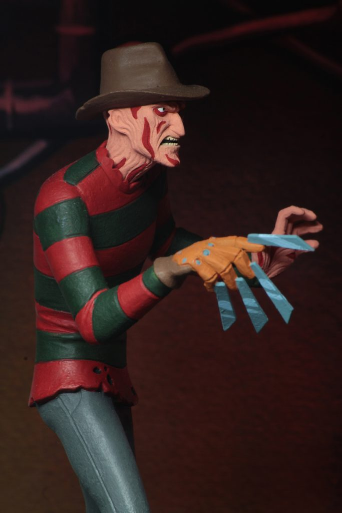 "This is a A Nightmare On Elm Street Freddy Krueger posable NECA 6"" action figure with blood on his face, who has a glove with blades and is wearing a red and green striped sweater, brown hat and grey pants."