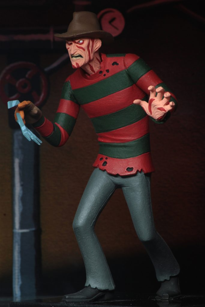 This is a NECA Toony Terror action figure of Nightmare On Elm Street Freddy Krueger, who is wearing a brown hat, red and green sweater, pants and boots.