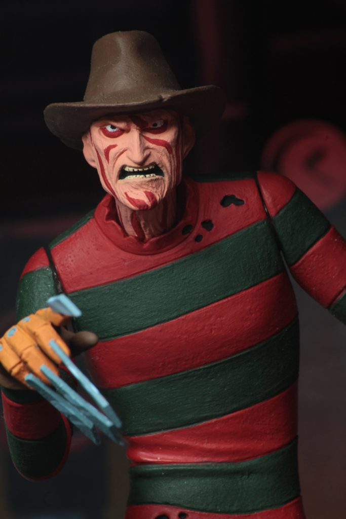 "This is a A Nightmare On Elm Street Freddy Krueger posable NECA 6"" action figure, who has a glove with 5 knives and is wearing a red and green striped sweater, brown hat and green pants."