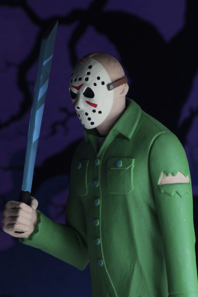"This is a Friday the 13th Jason Voorhees NECA 6"" action figure, who is holding a machete and wearing a green shirt, brown pants and a hockey mask."