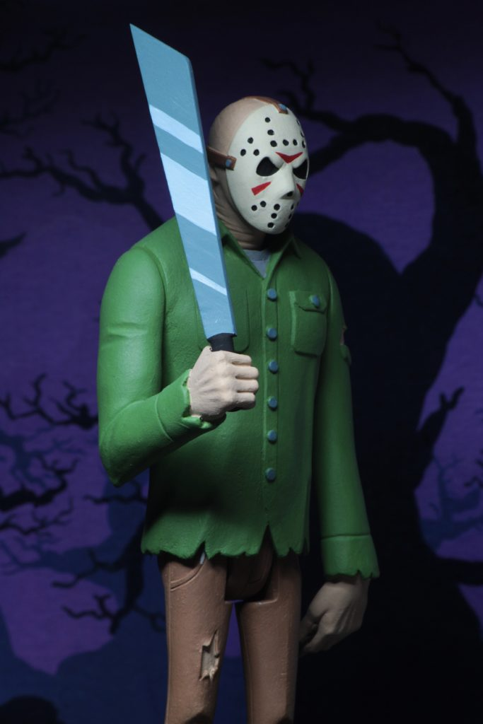 "This is a Friday the 13th Jason Voorhees posable NECA 6"" action figure, who is holding a machete and wearing a green shirt, brown pants and a hockey mask."