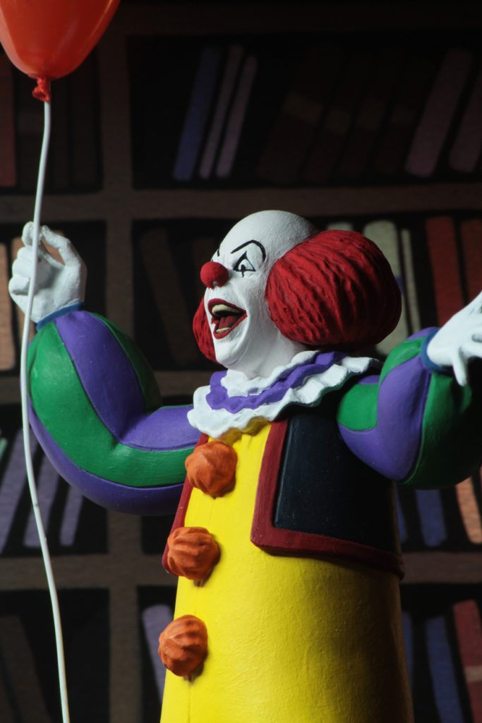"This is a Toony Terrors It 1990 miniseries Pennywise the clown posable NECA 6"" action figure, who is wearing a yellow clown suit with red balls, holding a red ballon and who has a red nose."