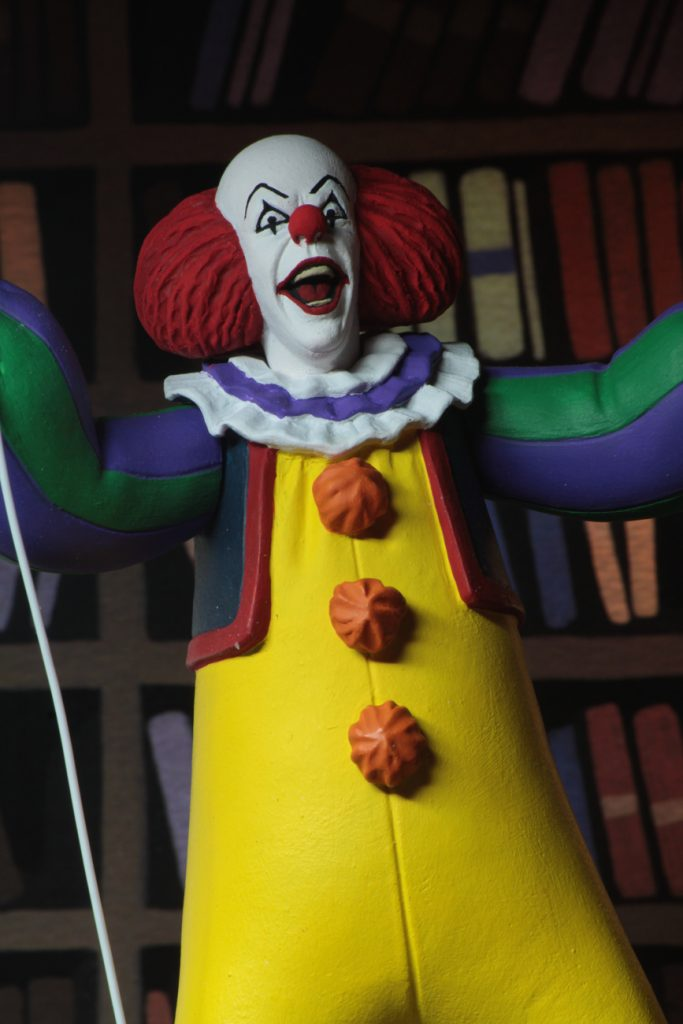 "This is a Toony Terrors It 1990 miniseries Pennywise the clown posable NECA 6"" action figure, who is wearing a yellow clown suit with red balls, white gloves, holding a red ballon and who has a red nose."