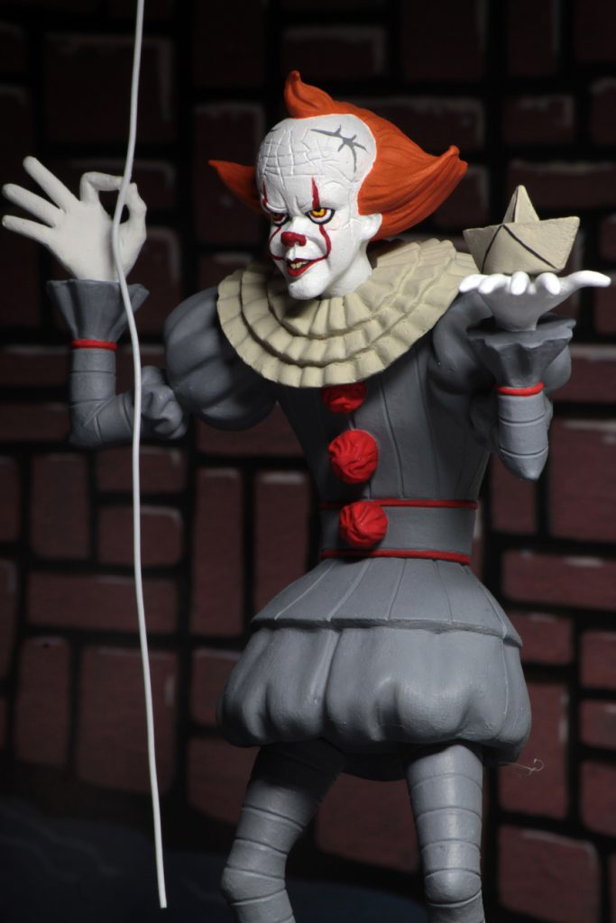 "This is a Toony Terrors It 2017 movie of a Pennywise the clown posable NECA 6"" action figure, who is wearing a grey clown suit with red balls, white gloves, holding a red ballon and who has a red nose and white face."