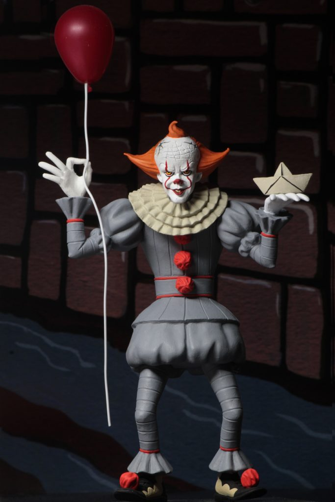 This is a NECA Toony Terrors It 2017 Pennywise action figure and he is wearing a grey clown suit that has three red balls and a white collar, with white gloves, balls on his shoes, a white face and orange hair and is holding a white boat and red balloon.