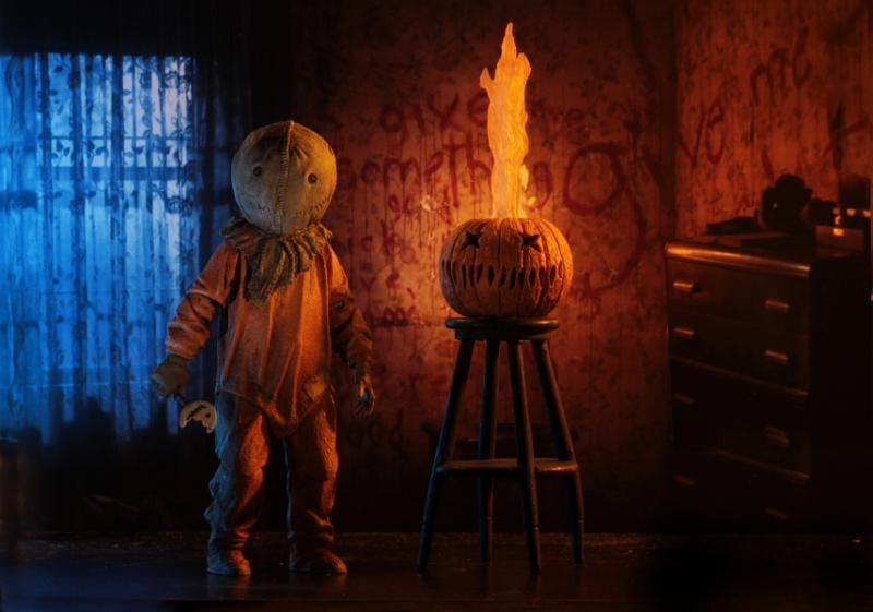 "This is a Trick R Treat Sam NECA 7"" ultimate action figure and there is a on orange pumpkin on a stool with the teeth and eyes cut out and fire coming out of it and he is wearing an orange suit, burlap mask, gloves and is holding a bitten lollipop."