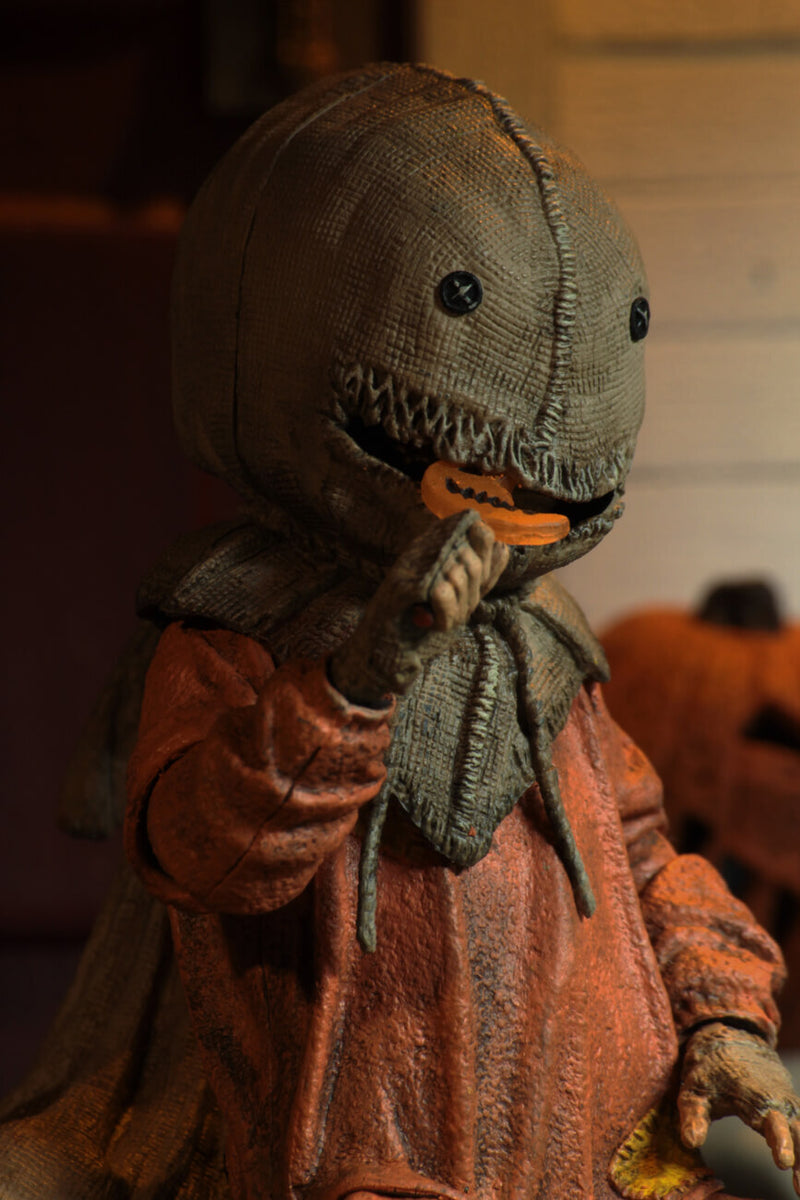 "This is a Trick R Treat Sam NECA 7"" ultimate action figure and he has a burlap mask, an orange suit, gloves and an orange lollipop."