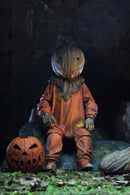 "This is a Trick R Treat Sam NECA 7"" ultimate action figure and he has a burlap mask, an orange suit, gloves and a pumpkin on the ground."