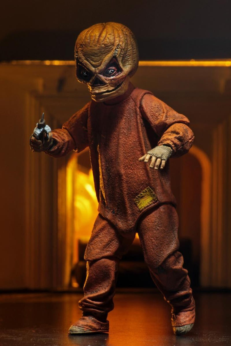 "This is a Trick R Treat Sam NECA 7"" ultimate action figure and he has a mask with triangle eyes, an orange suit, gloves and he is holding a candy bar knife."