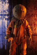 "This is a Trick R Treat Sam NECA 7"" ultimate action figure and he has a burlap mask, an orange suit, gloves and he is holding a bitten pumpkin lollipop."