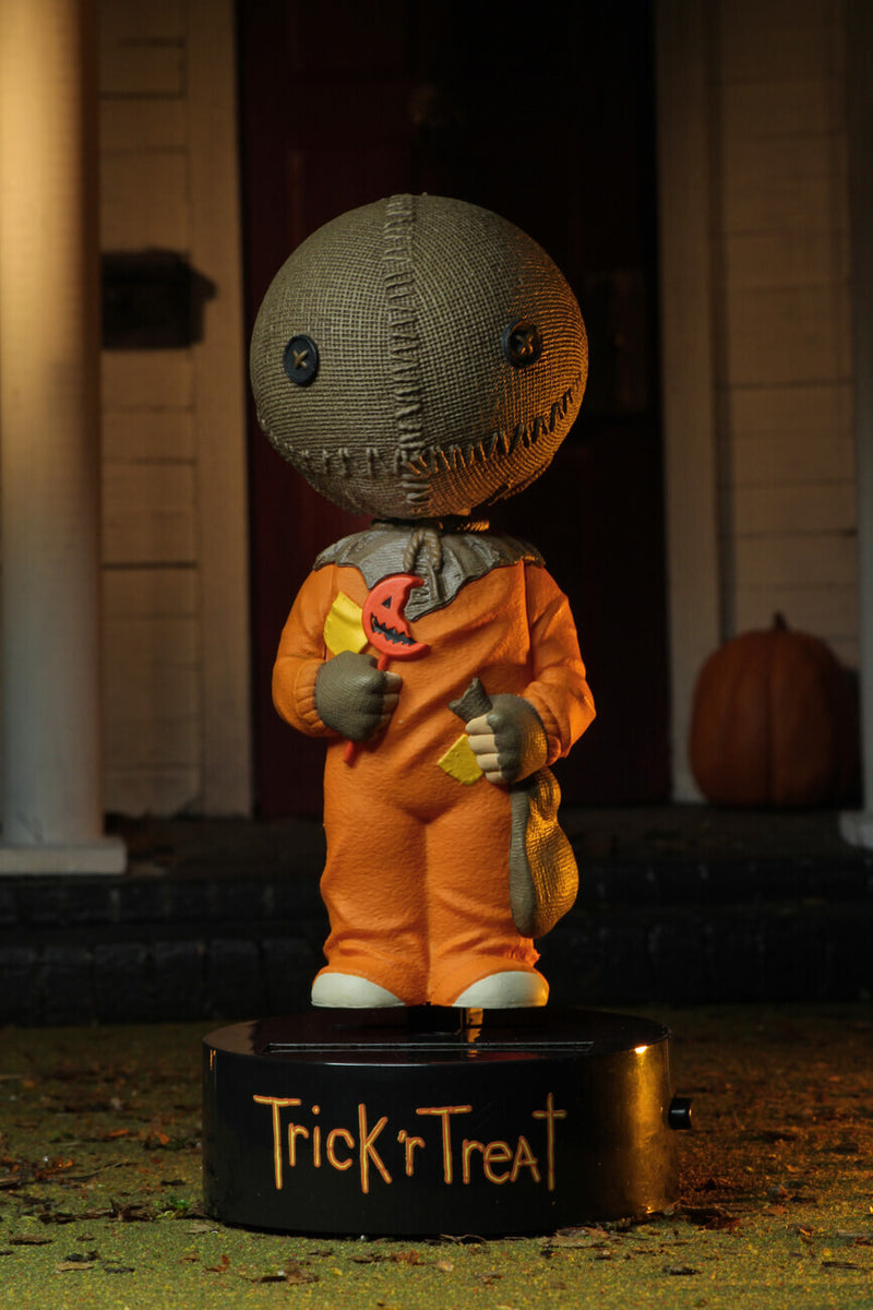 "This is a Trick ""r Treat Sam NECA Body Knocker and he has a plastic black base, brown burlap head, orange suit and a bitten orange lollipop and pumpkin in the background."