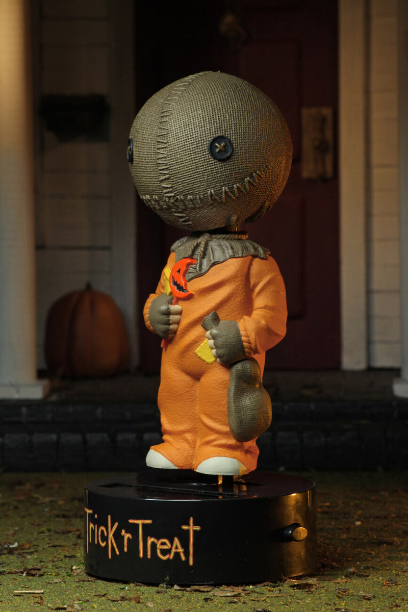 "This is a Trick ""r Treat Sam NECA Body Knocker and he has a plastic black base, brown burlap head, orange suit and a bitten orange lollipop and a rope on his neck."