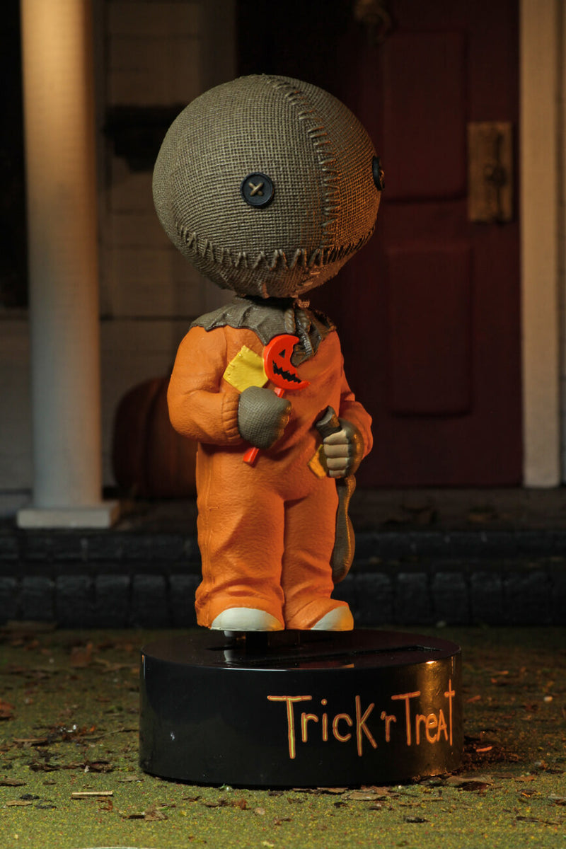 "This is a Trick ""r Treat Sam NECA Body Knocker and he has a plastic black base, brown burlap head, orange suit and a bitten orange lollipop in front of an yellow patch.."