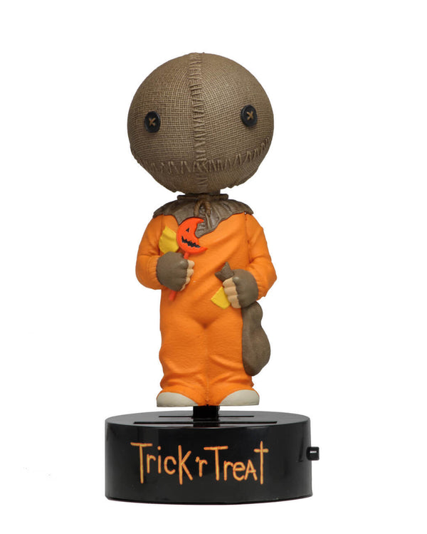 "This is a Trick ""r Treat Sam NECA Body Knocker and he has a plastic black base, brown burlap head, orange suit and a bitten orange lollipop."