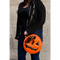This is a Trick 'R Treat Sam bitten lollipop purse and it is orange, with a black eye and smile, has a black strap and is on a person who is wearing jeans and a black sweatshirt..
