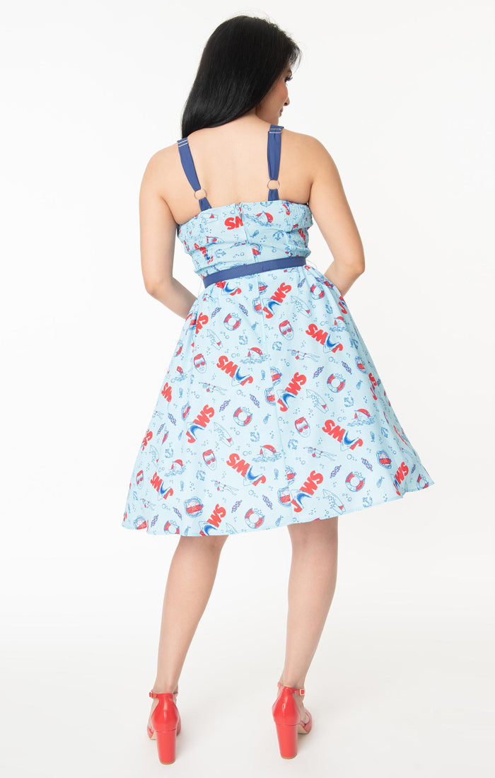This is a Unique Vintage Jaws dress and the model has dark hair, red shoes and the dress is blue with red text and sharks on it, a blue belt and a blue sweetheart neckline.