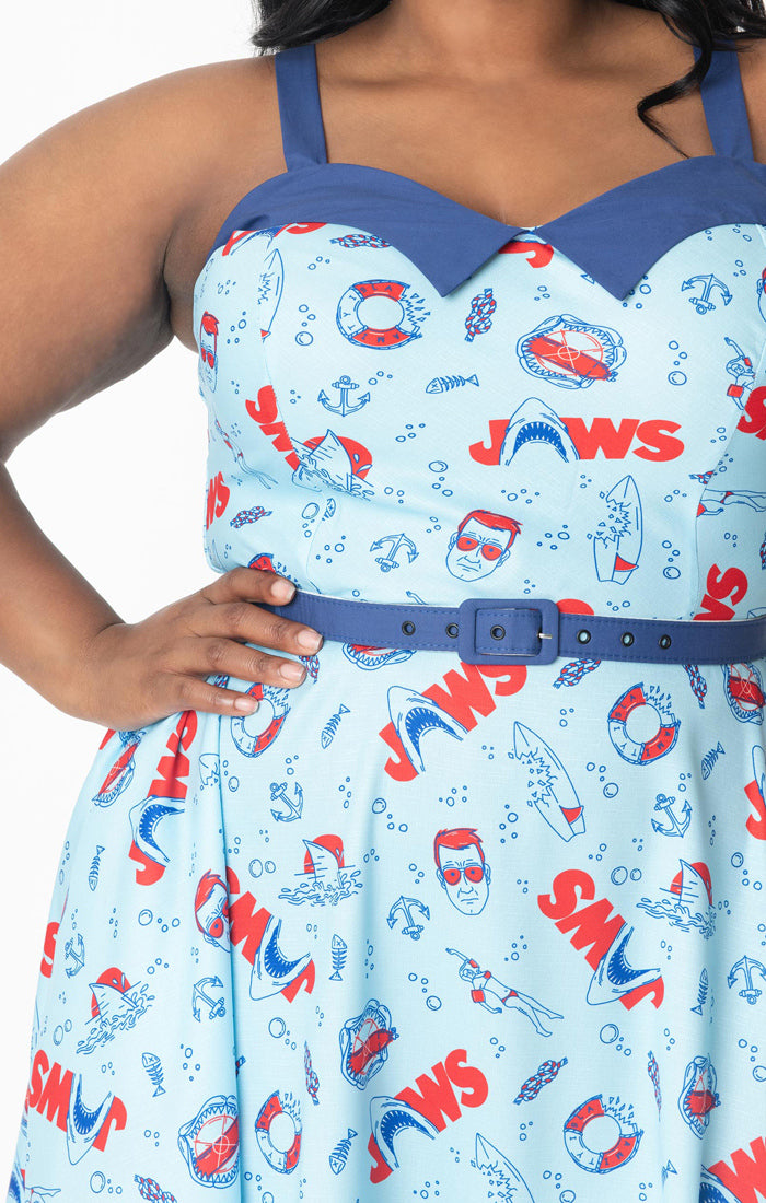 This is a Jaws dress that is light blue and has red text, sharks, lifesavers, Chief Brody and bitten surfboards.
