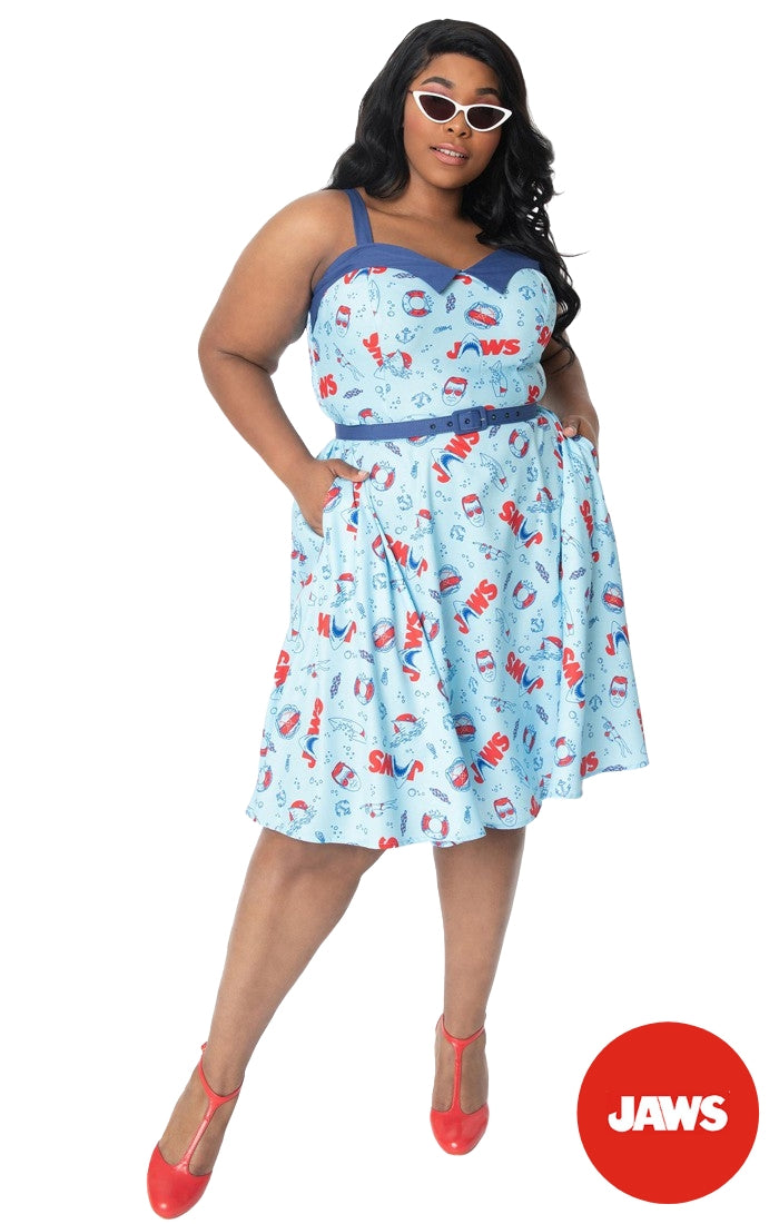 This is a Unique Vintage Jaws dress and the model has dark hair, red shoes and the dress is blue with red text and sharks on it, worn by a plus size model.
