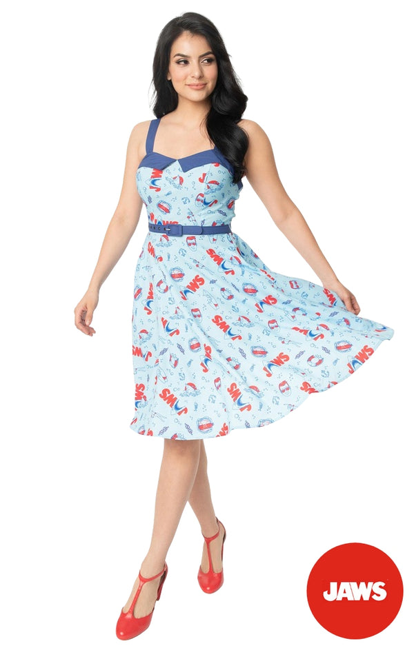 This is a Unique Vintage Jaws dress and the model has dark hair, red shoes and the dress is blue with red text and sharks on it.