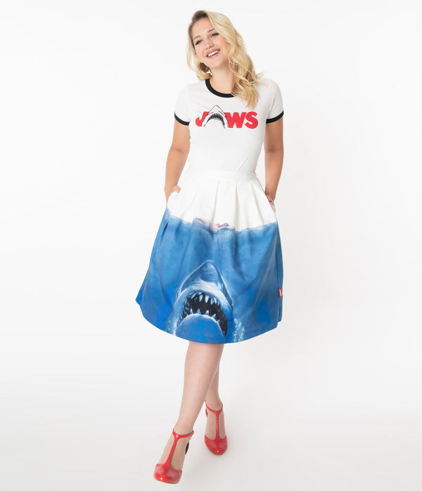 This is a Unique Vintage Jaws movie poster skirt and the model has blonde hair, red shoes and the skirt is white at the top, blue water on the bottom and a shark coming up to eat a swimmer.
